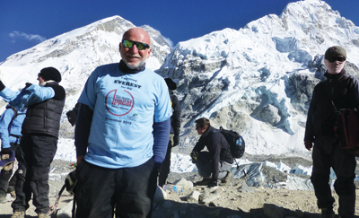Phil Frier in his office at K College. Inset: Frier completes his 2013 trek to Everest Base Camp