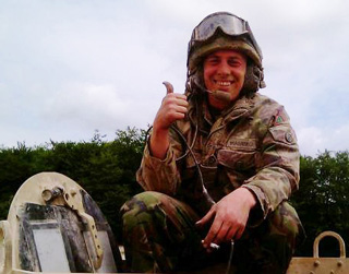 Murray perched on a tank while he was serving with the Army before the horrific landmine attack