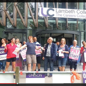 A still from a YouTube video of Lambeth College staff singing and dancing while picketing outside work.