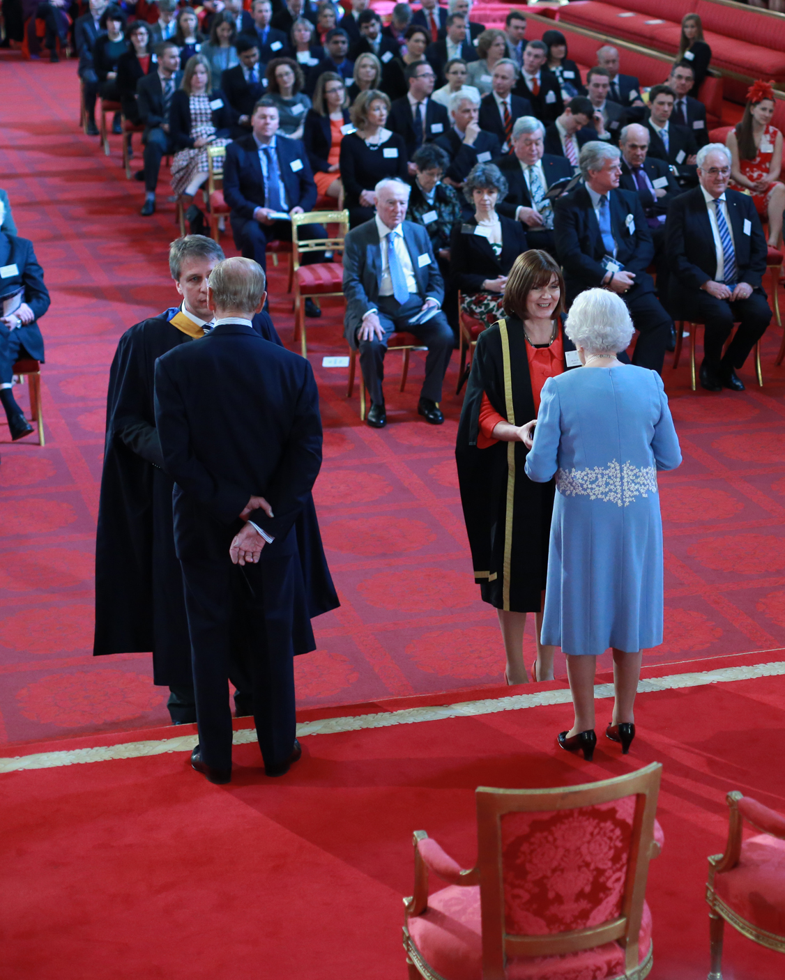 The Queen and Prince Philip present medals and certificates to Sue McLeod and Andrew Brader, managing director of subsidiary firm MidKent College Training Services (MKCTS)
