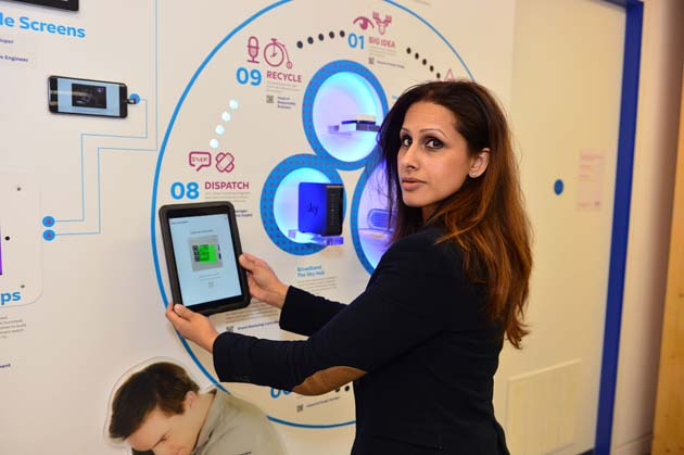 Nishy Lall, Sky Academy Manager standing by an interactive display showing apps and broadcasting technology