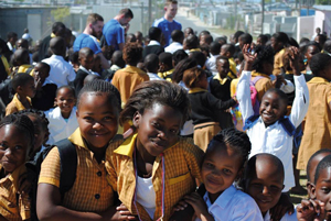 The Hugh Baird team get swamped by primary school children upon arriving in Cape Town