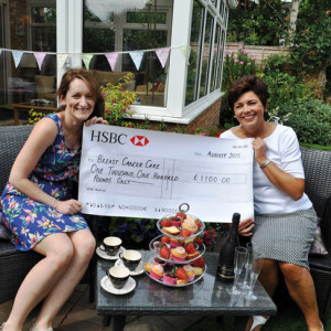 Marie Rowe and Vicky Brayne sit in Vicky's garden where the strawberry tea tookplacewiththechequeforBreastCancer Care