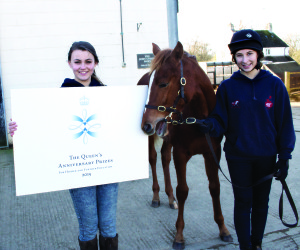 Abingdon and Witney College level three horse management students Naomi Flint, 17, and Alicia Plaistow, 16, holding a thoroughbred foal