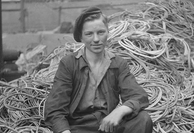 Apprenticeships-100-1---A-portrait-of-a-young-apprentice-fitter-as-he-sits-on-a-large-pile-of-cables-at-a-shipyardweb